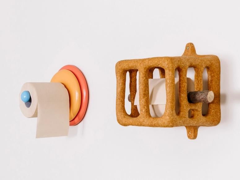 Two sculptural toilet paper holders.