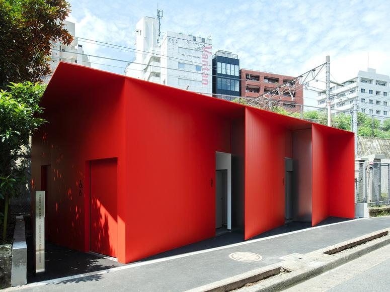 A bright red toilet building with angled entrances and the Tokyo cityscape in the background.