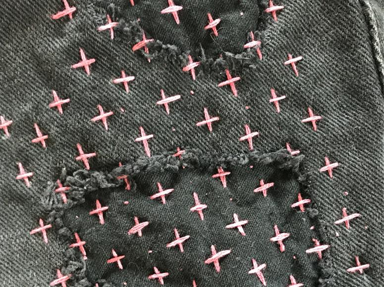 Black denim fabric with pink cross stitches