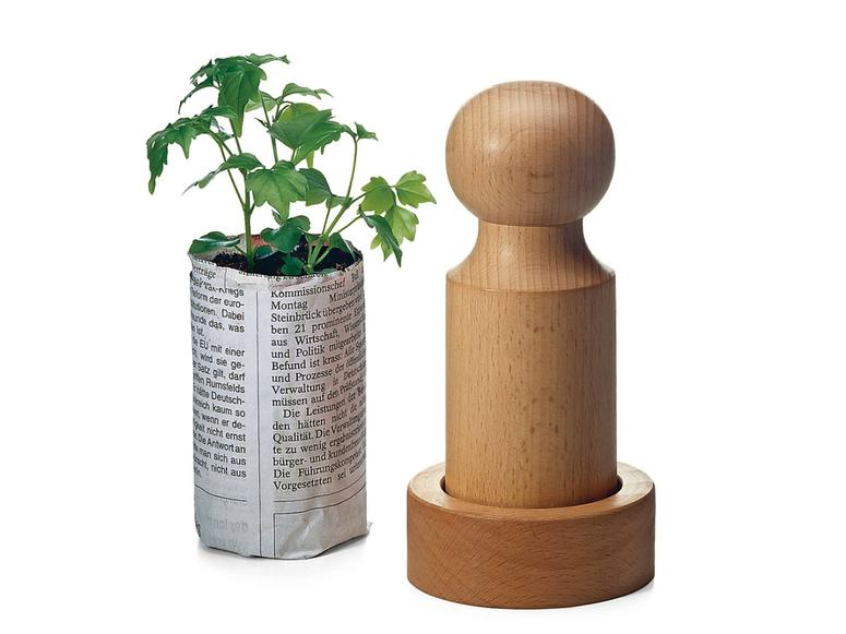 Manufactum's seed pot press next to a seedling.