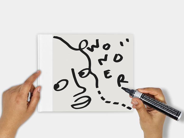 Shantell Martin's book, Wonder, with her hands holding a marker above it.