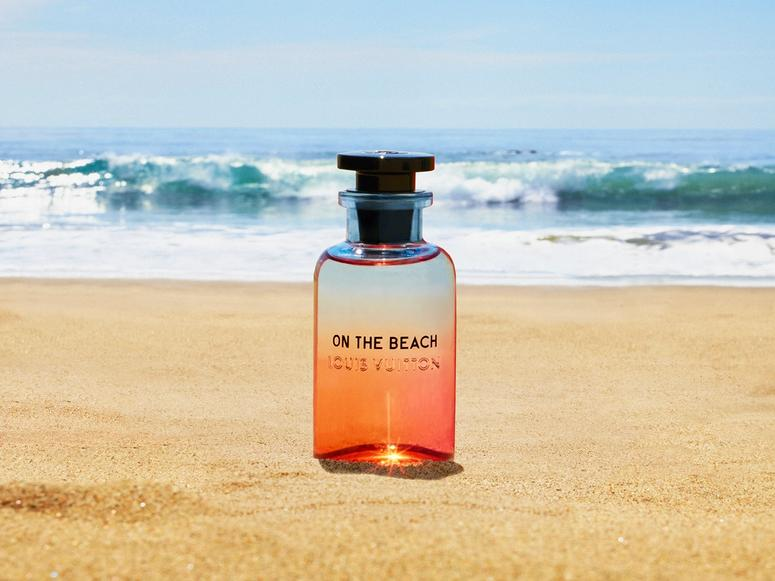 A glass bottle of perfume on a beach