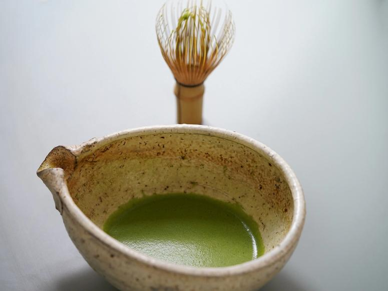 Matcha tea in a chawan in front of a matcha whisk.