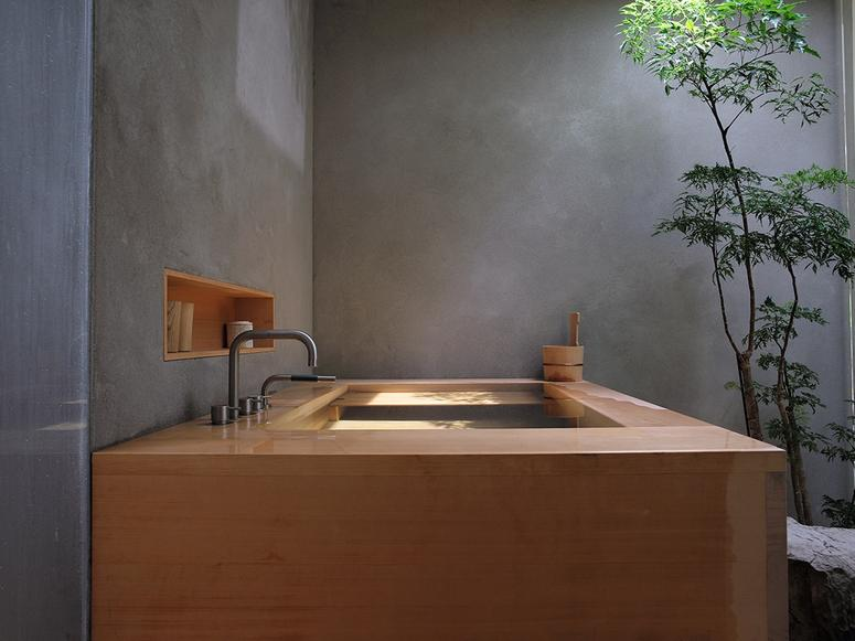 A hinoki bathtub in a concrete room with a small tree.