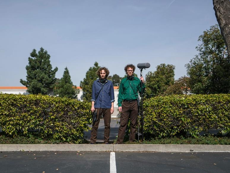 Sam Harnett and Chris Hoff holding audio equipment between two bushes in a parking lot.