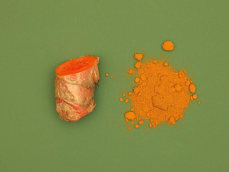 Bright Orange turmeric root and powder on a green background.