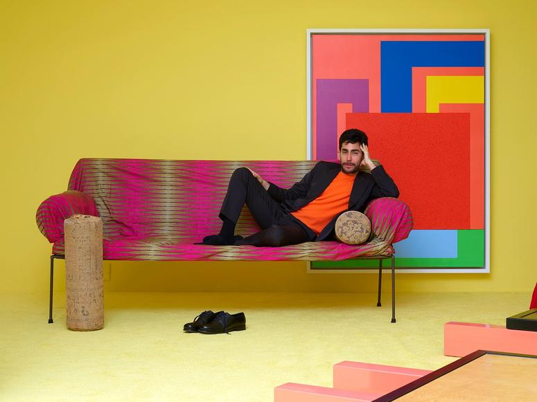 Omar Sosa reclining on a brightly colored couch in his brightly colored Friedman Benda show.