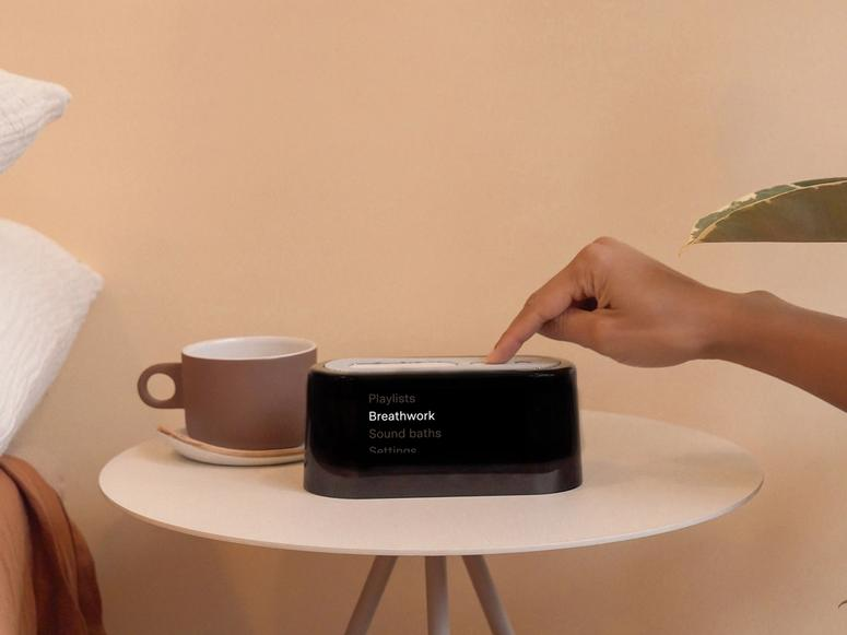 A black digital alarm clock on a pink bedside table