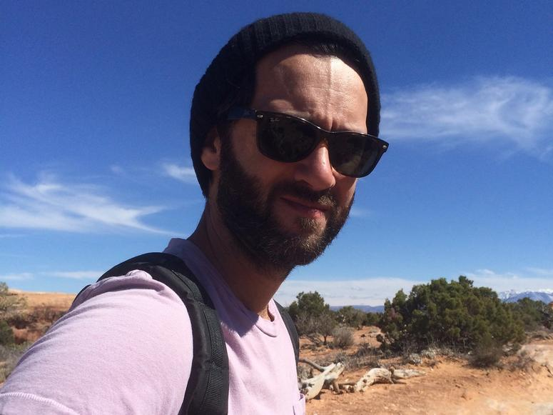 Keith Abramsson in sunglasses, walking through the desert.