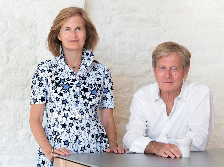 Catherine and John Pawson standing and siting at a table in front of a white wall.