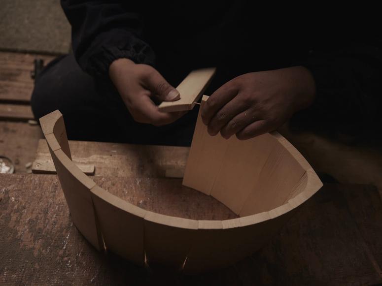 A man's hands assemble a wooden bucket on a wooden floor.