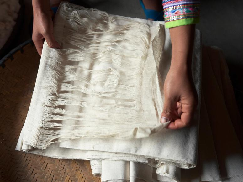 Hands holding the threads of a white roll of fabric.