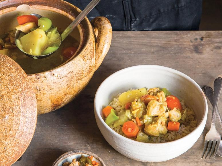 A ladle ladling Japanese chicken curry from a large clay pot into a bowl.