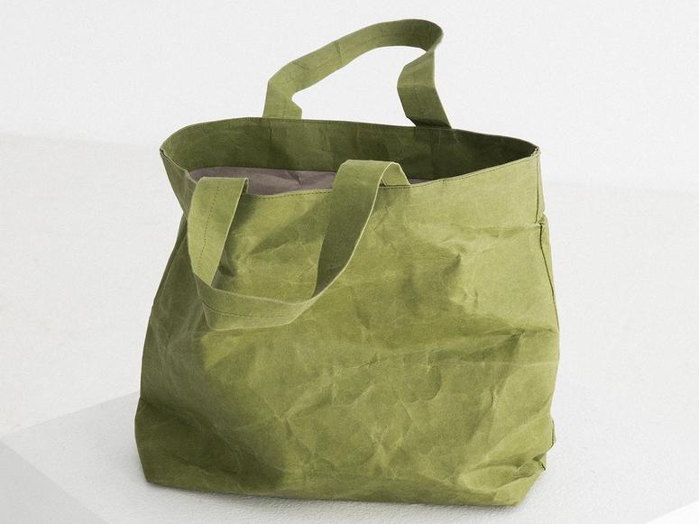 A crinkled green tote bag on a white plinth.