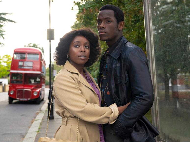 """A still from Steve McQueen's """"Small Axe"""" depicting two people holding each other on the street in London"""