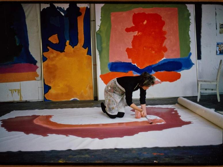 A woman kneels and paints a large rolled canvas on the ground, in front of other paintings lined up on a wall.