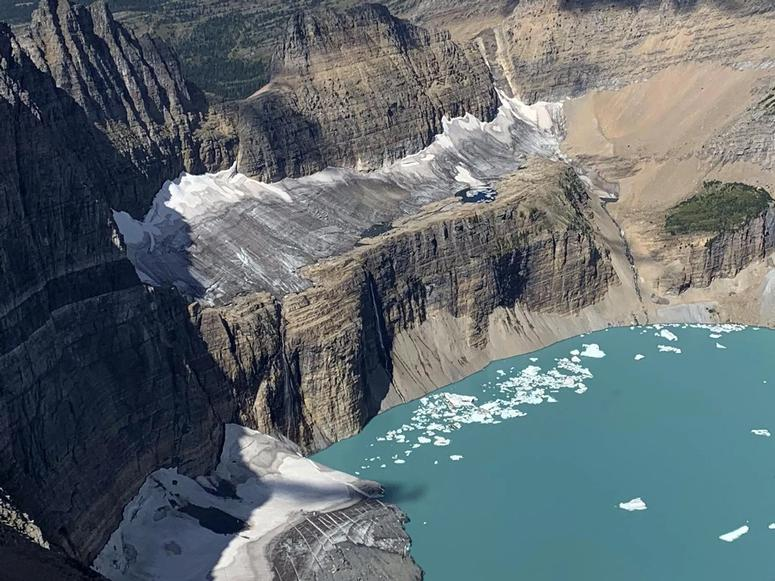 A large glacier on a cliff above the ocean.