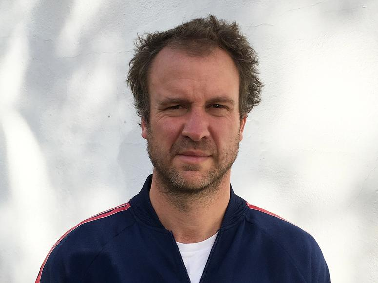 Malcolm James in a blue tracksuit, in front of a white background.