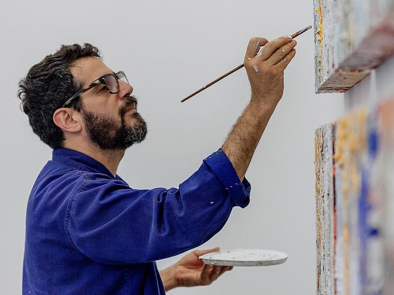 Jose Parla in a bright blue jacket and glasses, painting two canvases.