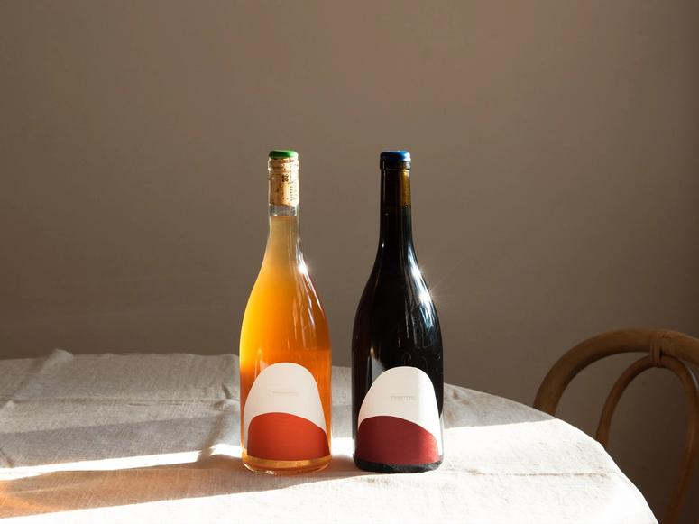 Orange and red bottles of wine in the sunlight on a natural linen tablecloth.