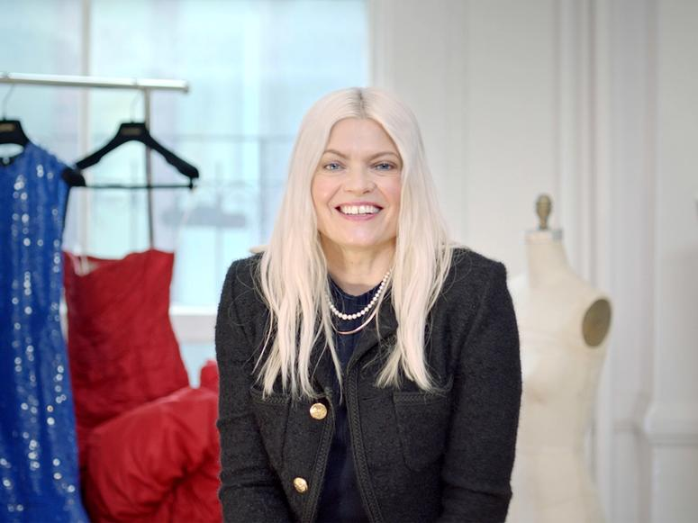 Stylist Kate Young in her office with high fashion dresses hanging in the background