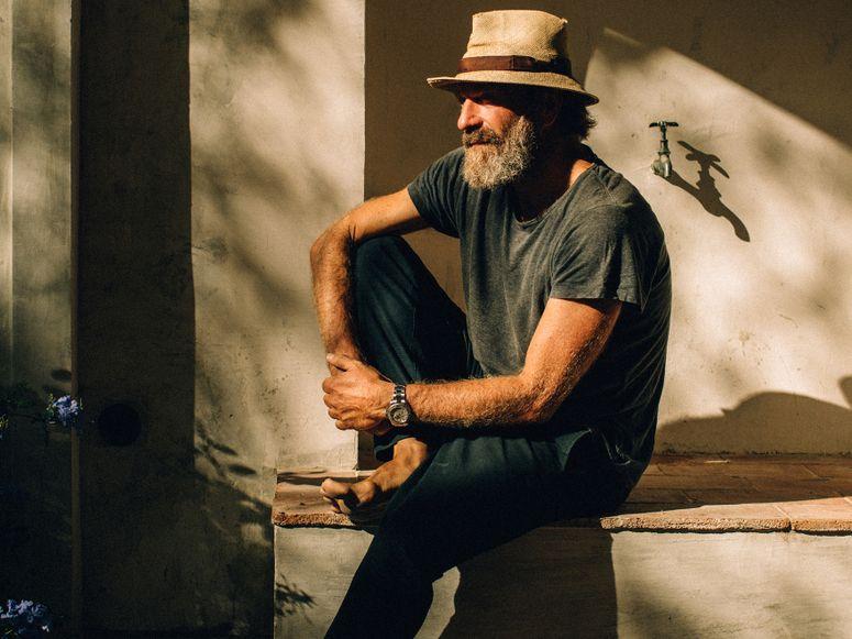 A man sitting outside barefoot wearing a hat