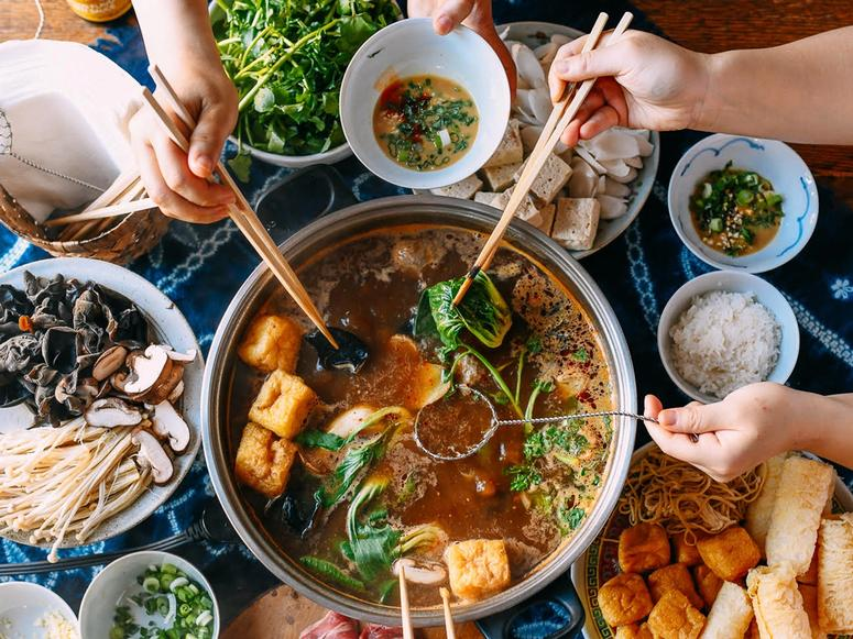 A large spread of dishes with three people adding various items to a hotpot.