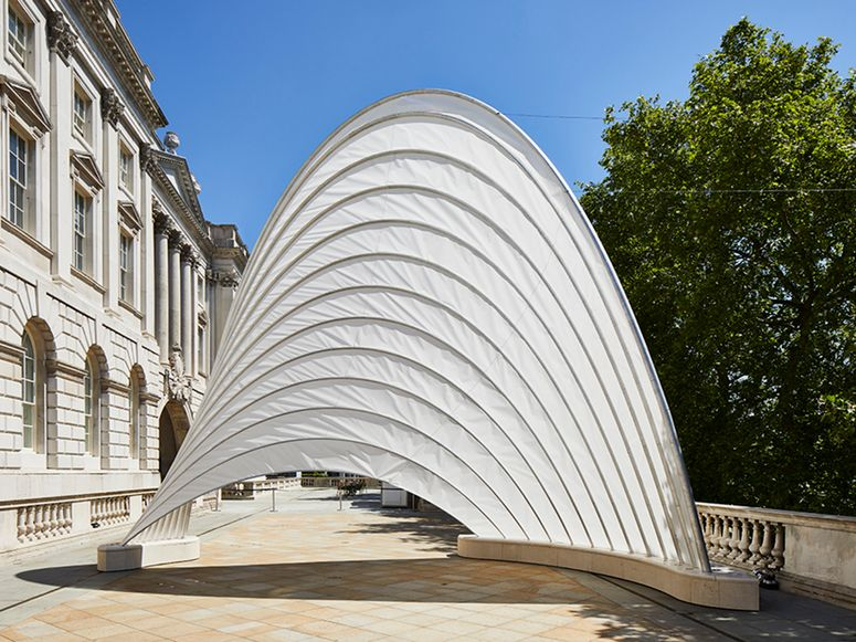 An arched white structure on a terrace