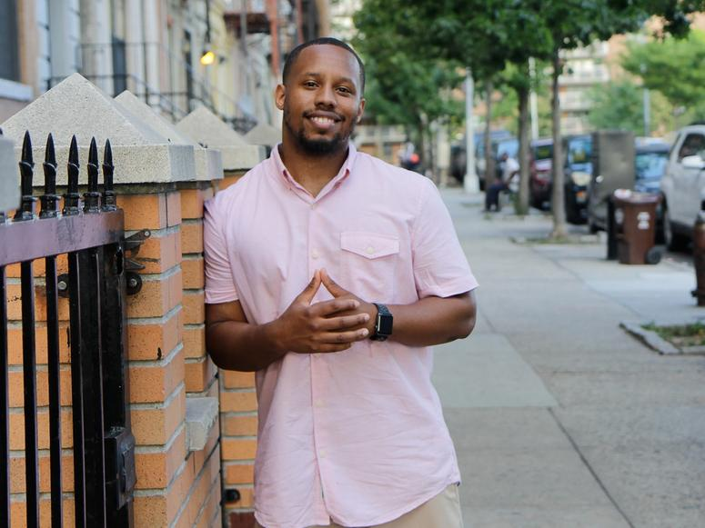 Eat Okra co-founder Anthony Edwards in a pink shirt on the sidewalk.