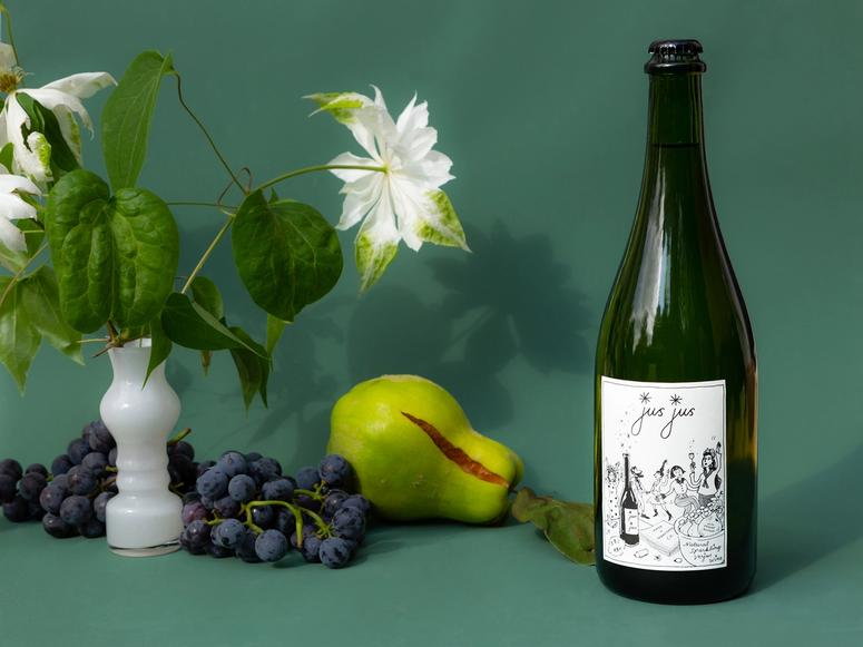 A bottle of Jus Jus next to a pear, purple grapes, and a white flower.