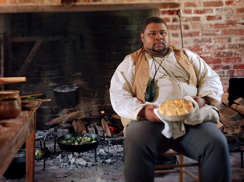 Michael W. Twitty sitting with a plate of biscuits in front of a large open fireplace.