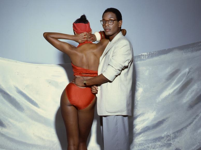 Willi Smith looking into the camera, his hand on a model with a red bathing suit, facing away.