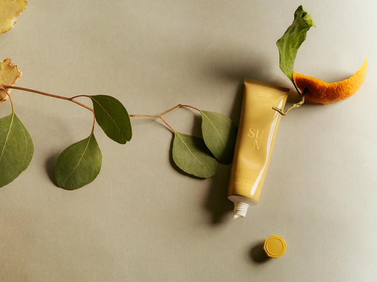 3rd Ritual's Sun balm in a yellow squeeze tube, on top of a leaf and orange rind.