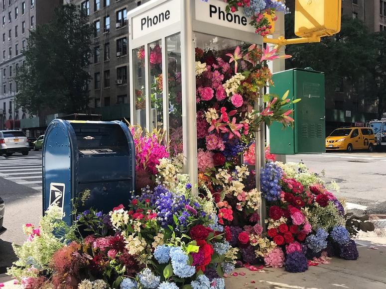 Hundreds of flowers spill out of a phone booth on on New York City street corner.