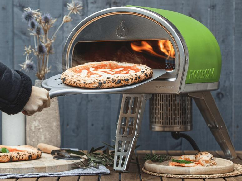 A hand pulling a steaming margherita pizza out of a green Roccbox oven.