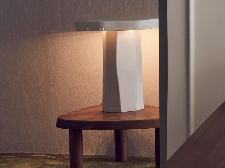 A white ceramic lamp on a wood table.