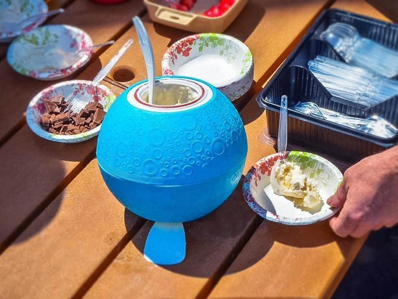 A ball used to make ice cream sitting on a picnic table