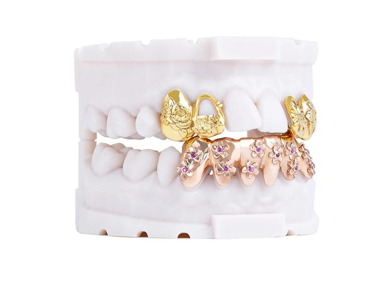 A pair of white denchers with gold and rose-gold grills.