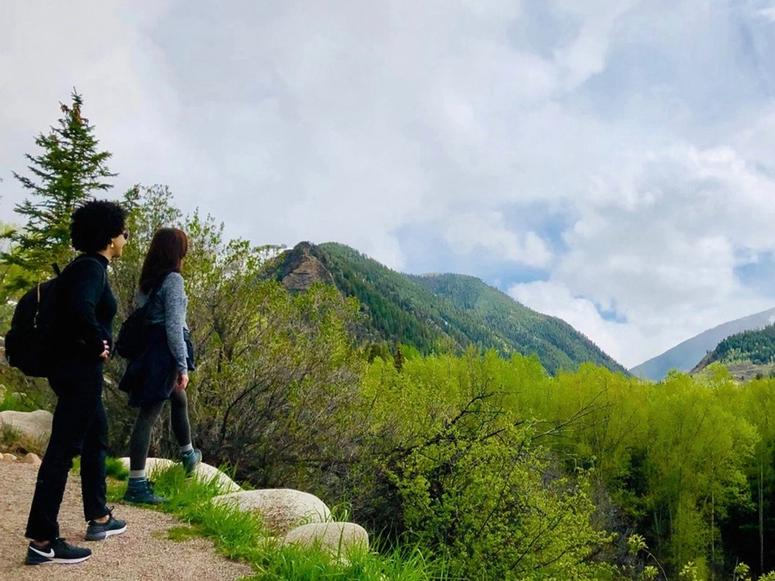 Dr. Ayana Elizabeth Johnson and Dr. Katharine K. Wilkinson looking out over green mountains from a patch of trail.