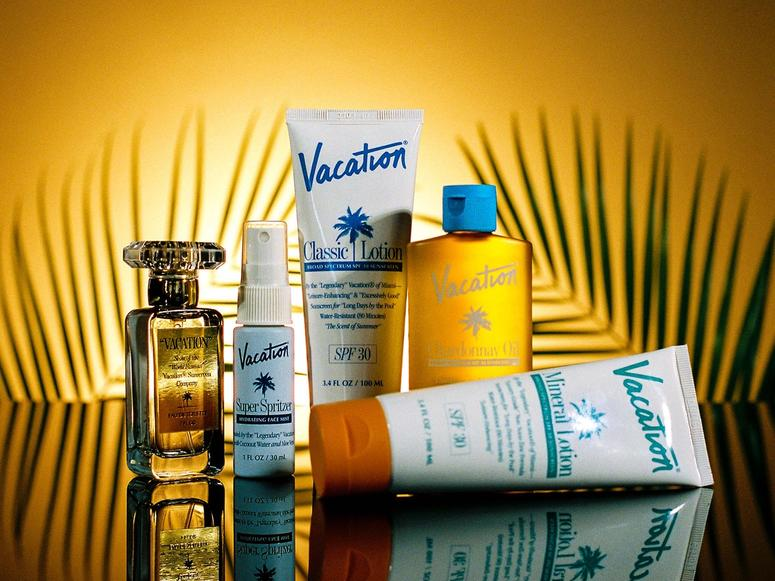 Tubes of sunscreen and a perfume shot in front of palm leaf branches