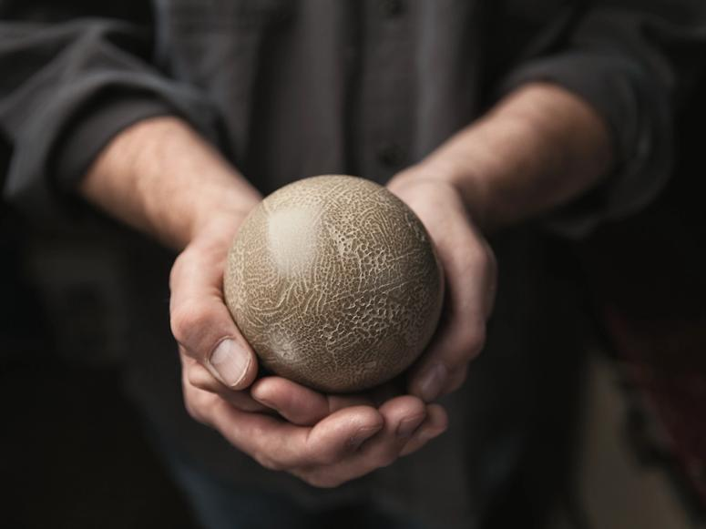 Two hands cupping a dorodango mud ball.