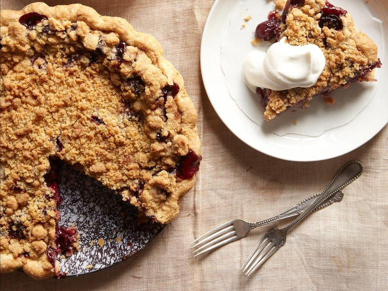 A crumble pie topped with whipped cream
