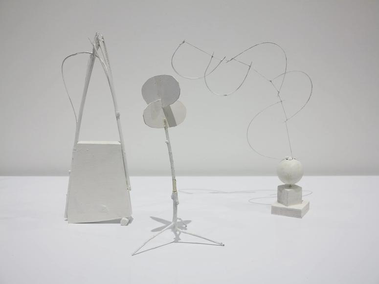 Three white, off-kilter sculptures on a white background.