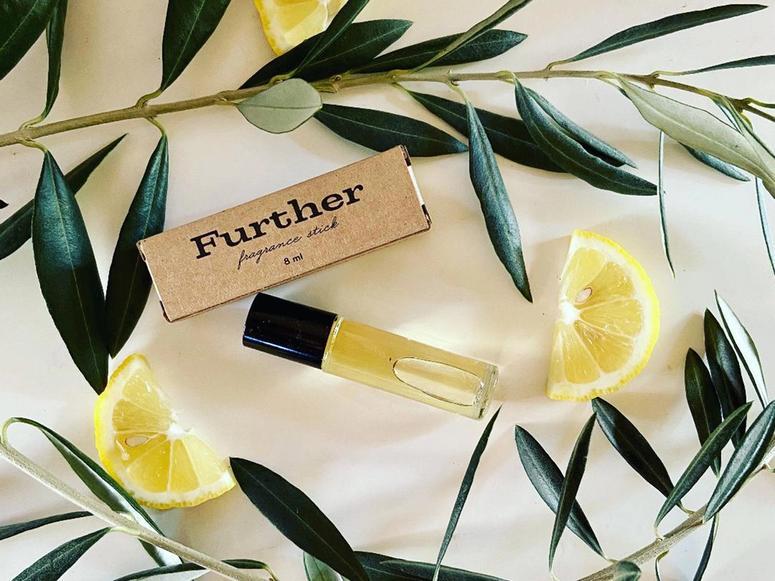 A vial of perfume among rosemary and slices of lemon.