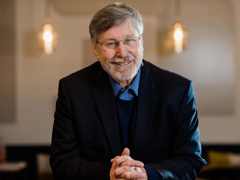 Dr. Bessel van der Kolk in a dark suit with his hands clasped, smiling.