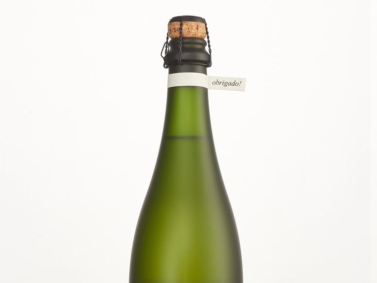 """A green bottle of brut with a small tag around its neck reading """"obrigado!"""""""