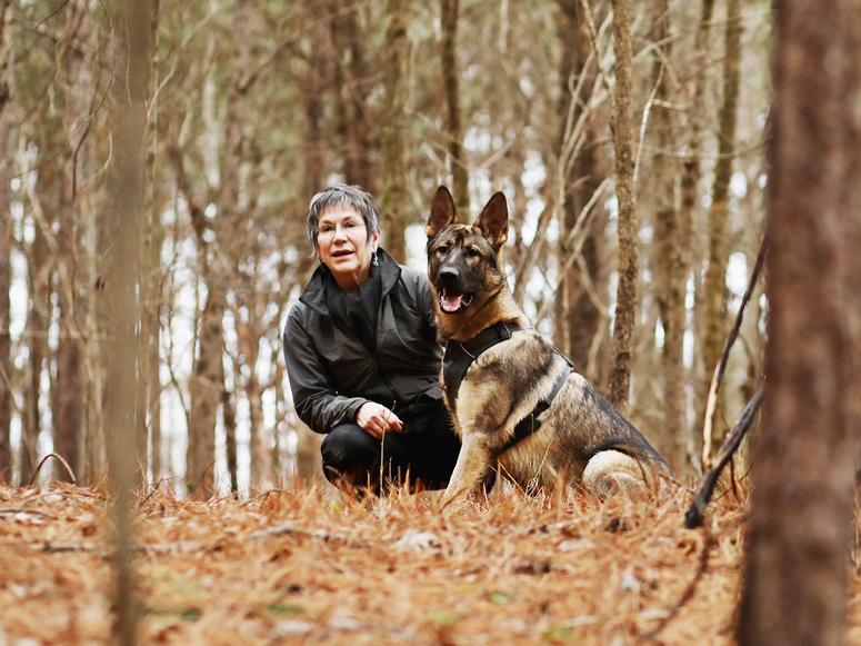 Author Cat Warren and one of her dogs, Rev, crouching in an autumn forest.
