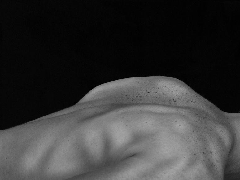 A person's bare back against a black background.