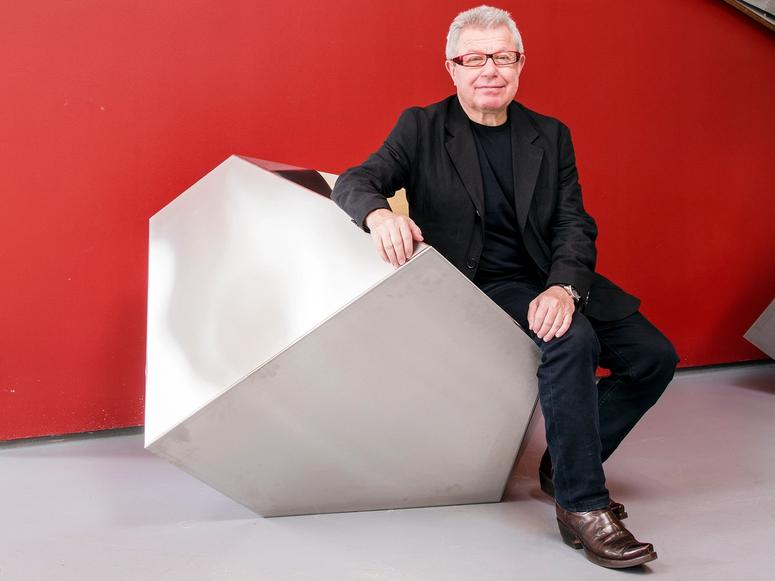Daniel Libeskind in a black suit in front of a red wall, sitting on a geometric seat.