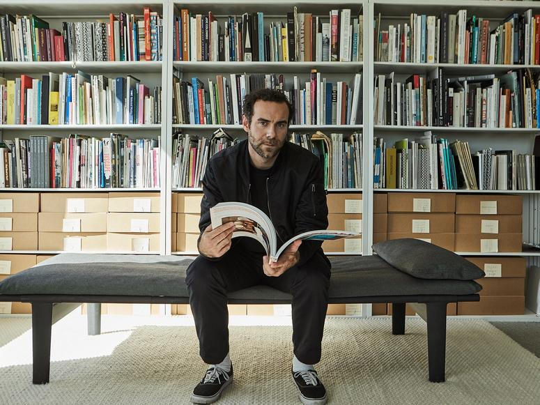 Jonathan Olivares sitting on a daybed in his library, reading a large art book.